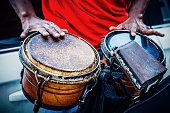 Hands of Cuban street band drummer hitting drums.