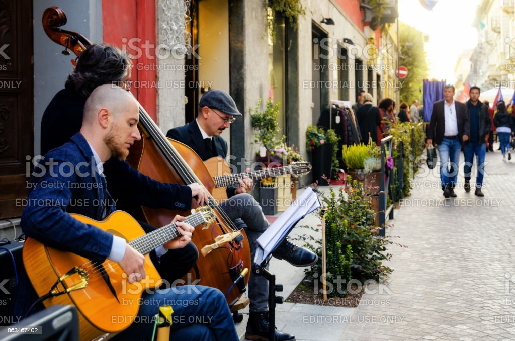 Street band playing music and tourists walking in the center of Alba (Piedmont, Italy) stock photo