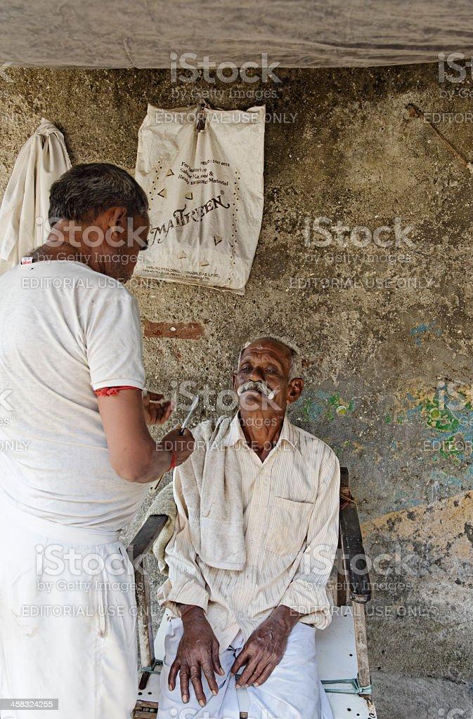 Street barber shaving old man in Mumbai, India royalty-free stock photo
