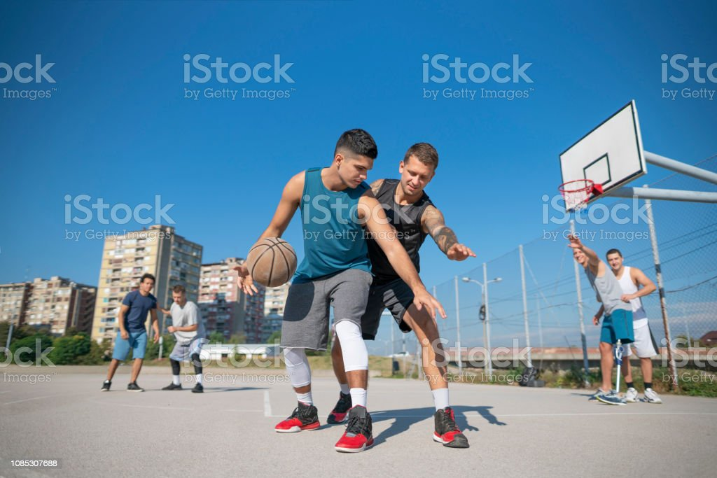 Group of friends playing street basket in their neighborhood.