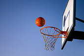 istock Street basketball ball falling into the hoop. Close up of orange ball above the hoop net with blue sky in the background. Concept of success, scoring points and winning. Copy space 1224208557