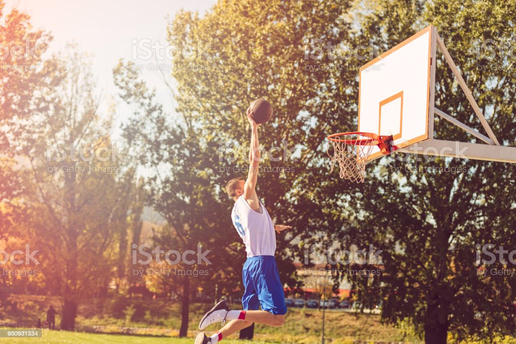 Street basketball player performing power slum dunk stock photo