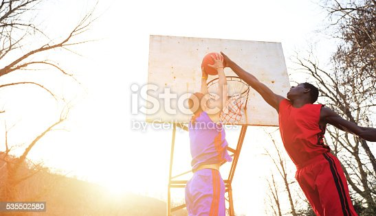Caucasian and african basketball players practice outdoor at sunset. Low angle view. Trees and sunlight on background.