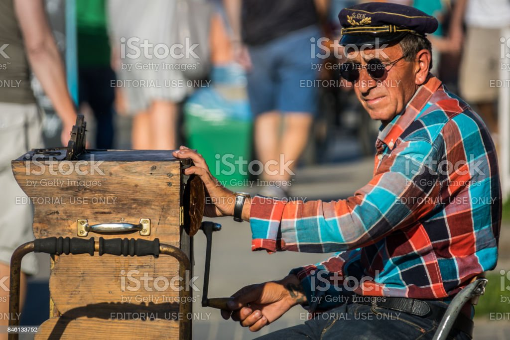 Street busker playing organette stock photo