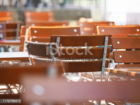 647209792 istock photo Street cafe background. Wooden tables and chairs 1170750412