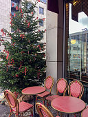 istock Street cafe near Christmas tree with red ornaments outside. 1328733913