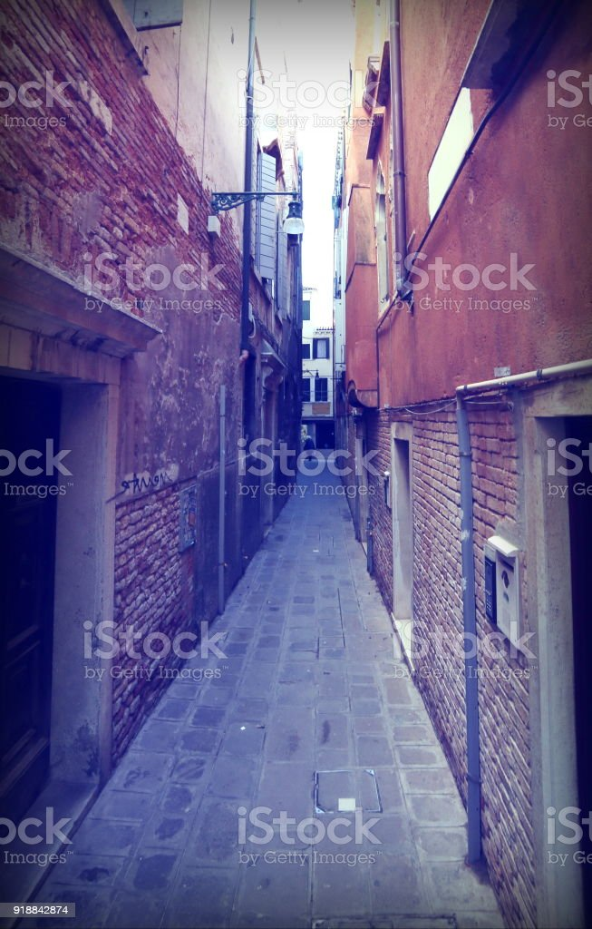 street called CALLE in Italian Language  between tall houses in Venice Italy stock photo