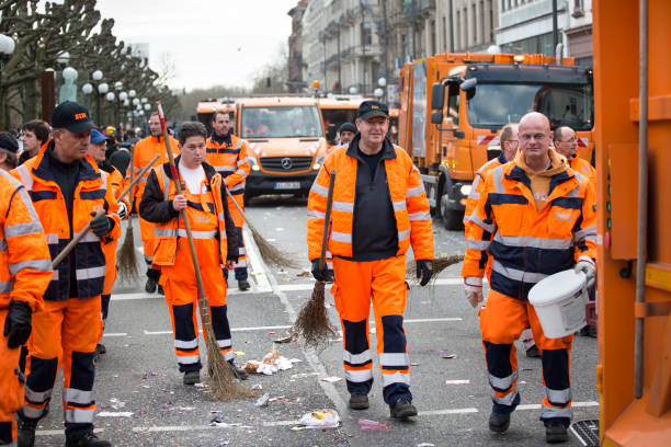 Street carnival Wiesbaden 2017 - cleaning the streets Wiesbaden, Germany - February 26, 2017: Carnival 2017. Street cleaners start with their hard work shortly after the end of the carnivals parade that moved through the streets of Wiesbaden, Germany. street sweeper stock pictures, royalty-free photos & images