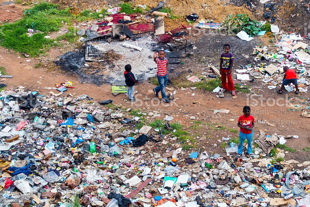 Street children playing at a dumpsite stock photo