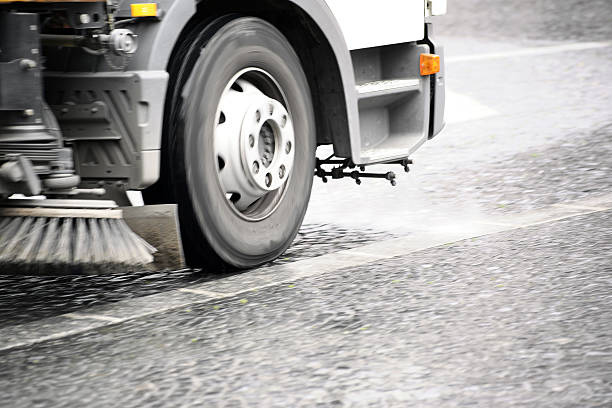 Street cleaning vehicle A road sweeping vehicle adjusted a sidewalk with cobblestones of dirt. street sweeper stock pictures, royalty-free photos & images