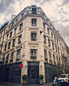 Paris, France - May 1, 2017: Street corner in Paris with cars parked and restaurant closed, France. No people