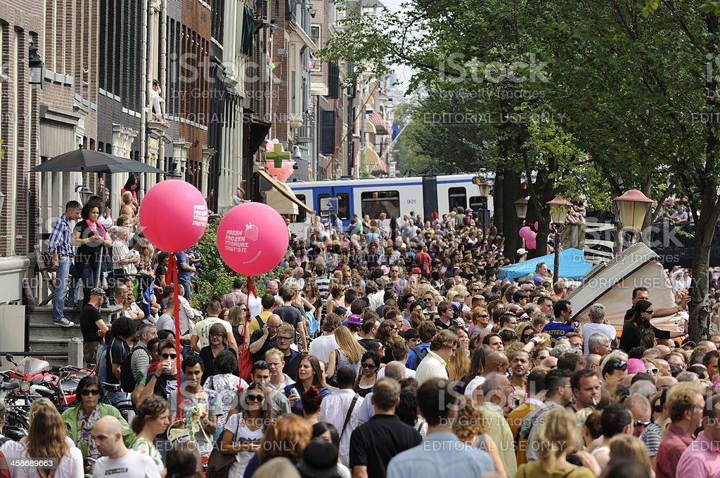 Street crowded with people watching the Amsterdam Canal Parade royalty-free stock photo