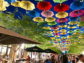 Miami, USA - September 16, 2018: Street at Coral Gables decorated with colored and open umbrellas, people enjoying the decoration.