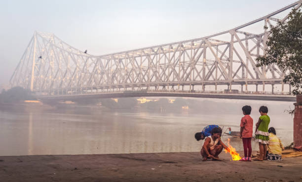 street dwellers keeping warm by burning fire on a winter morning near the historic howrah bridge at kolkata, india - disinherit stock pictures, royalty-free photos & images
