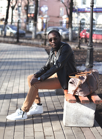 627398448 istock photo Street fashion concept african man with bag sits on bench 636345330