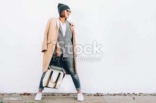 istock Street fashion look. Woman dressed in multilayered outfit for autumn days 1042685010