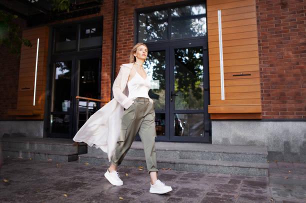 street fashion stijl. mooie sexy vrouw dragen modieuze lente of vallen kleren (beige trenchcoat, cargo broek, accessoire) buitenshuis. vrouwelijke stijlvolle model walking street. herfst trend - street style stockfoto's en -beelden