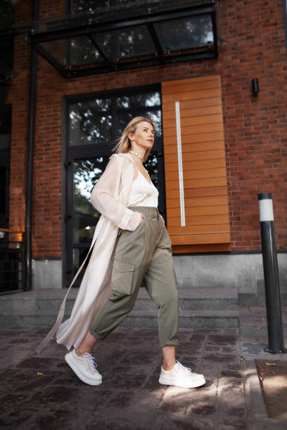 street fashion style. beautiful sexy woman wearing fashionable spring or fall clothes (beige trench coat, cargo pants, accessorie) outdoors. female stylish model walking street. autumn trend - spring fashion stock pictures, royalty-free photos & images