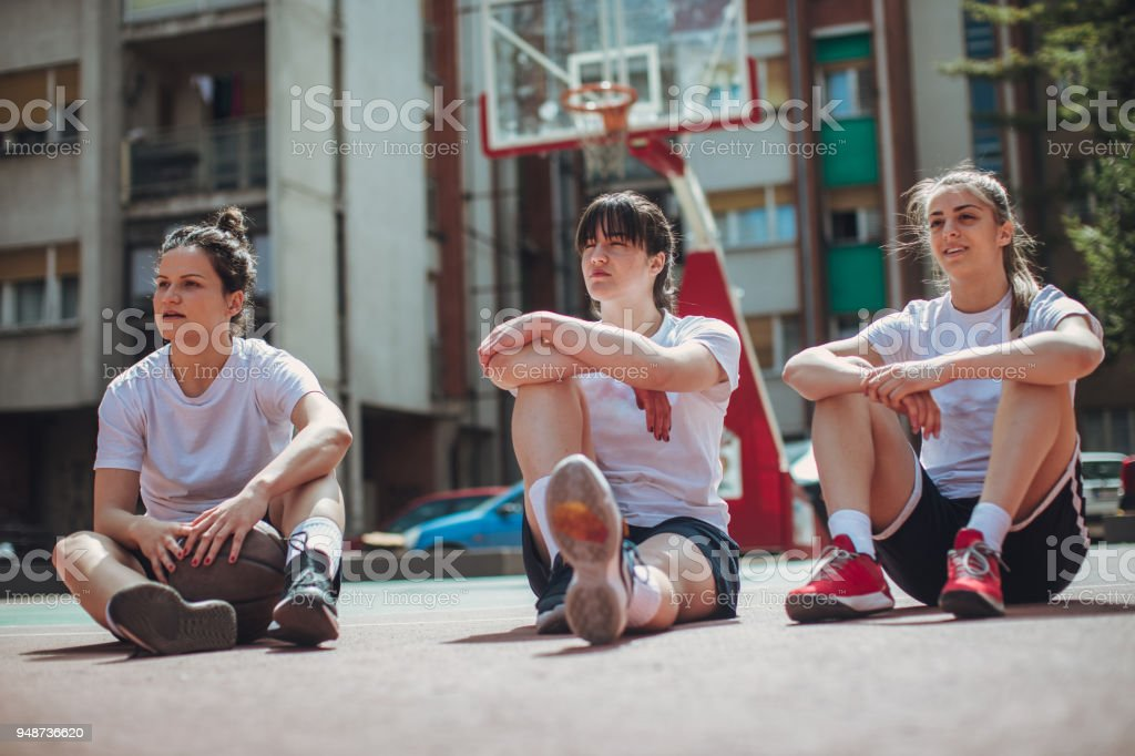 Street female basketball players sitting on the court stock photo