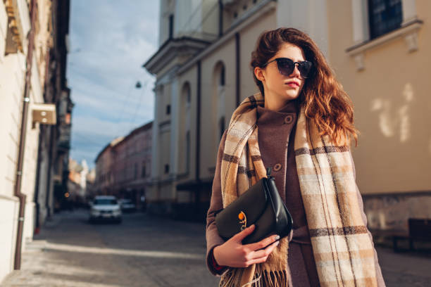 street female fashion. portrait of stylish young woman wearing coat glasses holding purse outdoors. spring accessories - spring fashion stock pictures, royalty-free photos & images