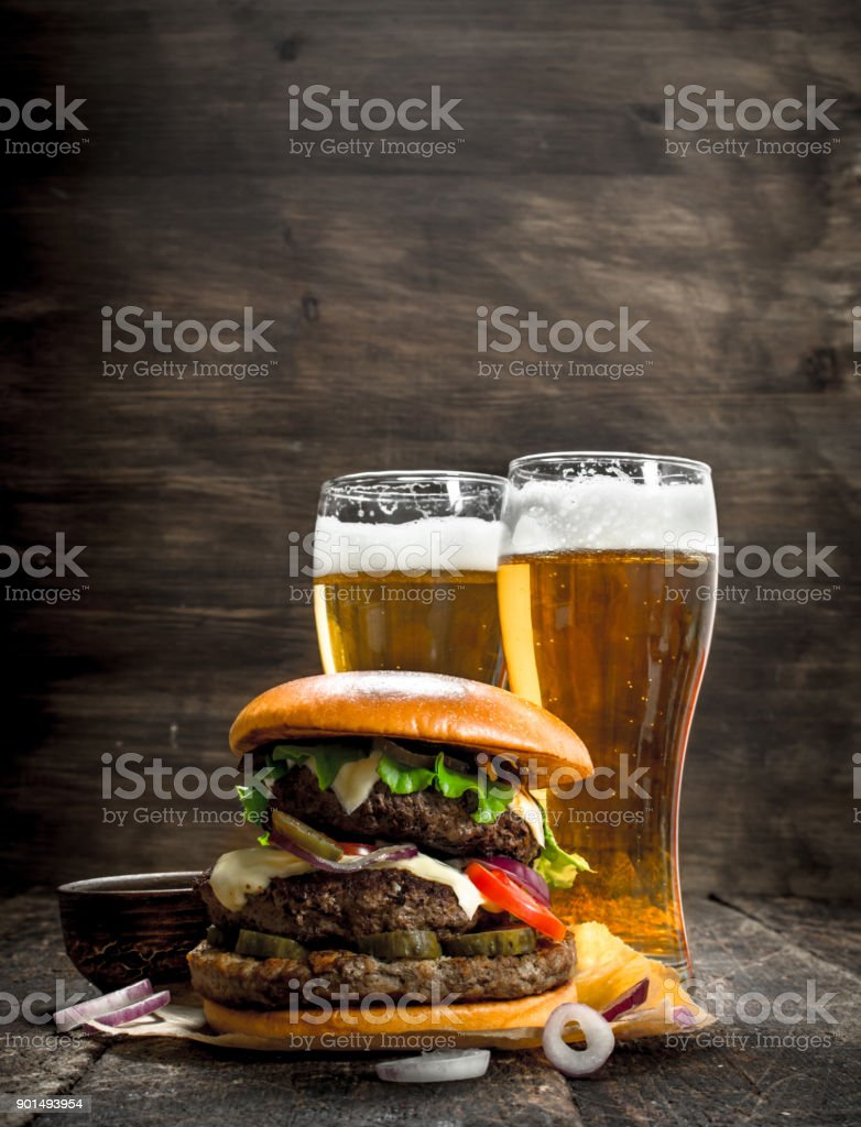 Street food. A big burger with glasses of light beer. stock photo