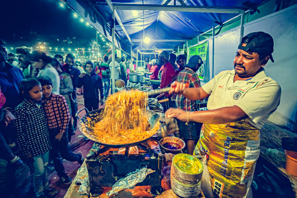 Street food chef makes and sells noodles at Himachal Utsav fair. stock photo