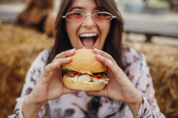 Street food festival. Stylish hipster girl in sunglasses eating delicious vegan burger at street food festival. Happy boho woman tasting and biting burger with vegetables in summer street. Street food festival. Stylish hipster girl in sunglasses eating delicious vegan burger at street food festival. Happy boho woman tasting and biting burger with vegetables in summer street. female sandwich stock pictures, royalty-free photos & images