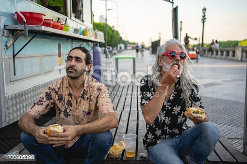 Two adult Hispanic men bying food from food truck in Buenis Aires, sitting on the ground and eating street food