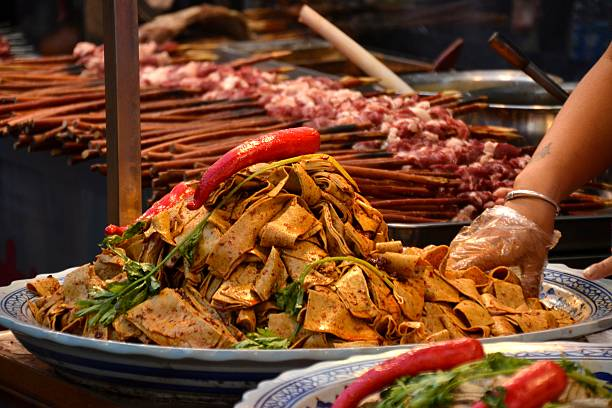 Street food in the muslim quarter of Xi'an, Shaanxi Big plate of spicy local noodles and lamb skewers in Huimin Street, in the Muslim Quarter of Xi'an. The area has become a famous attraction of Xi'an for its profound Muslim cultural atmosphere. muslim quarter stock pictures, royalty-free photos & images