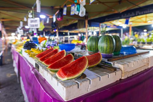 Street food night market at  Putrajaya, near Kuala Lumpur. Red fresh watermelon on the counter. Watermelon cut into quarters at a stand in the fresh market