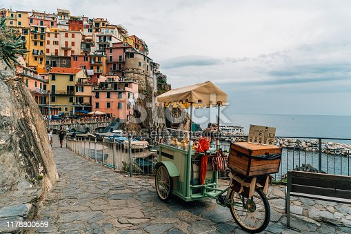 View of a street food stall on a bicycle in the street in the coastal old town of Manarola and houses on a hill in the background, Cinque Terre, Liguria, Italy