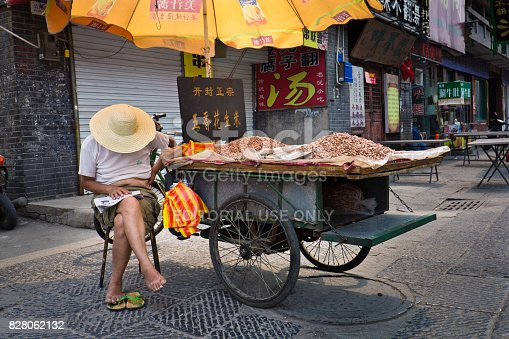 A street food vender selling roasted peanuts taking a rest with his food cart at the old town district of Xian, China. A popular shopping and entertainment district of the city. International tourists and local residents frequent the area for its retail shops, street food, famous restaurants and eateries. Photographed May 21, 2017.