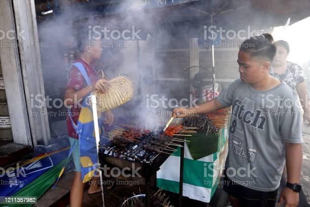Street food vendor at her food stall sells grilled pork and chicken picture id1211357982?b=1&k=6&m=1211357982&s=612x612&h=6s9zbwvhsjckmkip68oz trmxvqj007encbjvbz5weq=