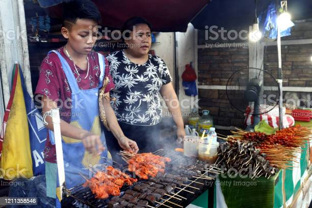 Street food vendor at her food stall sells grilled pork and chicken picture id1211358546?b=1&k=6&m=1211358546&s=612x612&h=qm1blybby7wg amf4hzdsbzhuay1vjxwpu4ecjwvf7u=