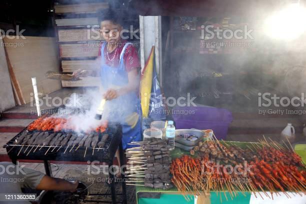 Street food vendor at her food stall sells grilled pork and chicken picture id1211360383?b=1&k=6&m=1211360383&s=612x612&h=8sbijaagostqmfdmnkwyj9ss6p wxnwnaaqpihyge4u=