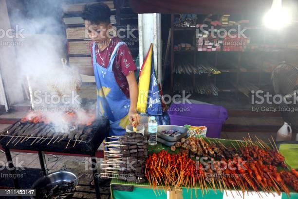 Street food vendor at her food stall sells grilled pork and chicken picture id1211453147?b=1&k=6&m=1211453147&s=612x612&h=kx8fdqvc2mycxgzsfanxqm07bemxcgykqgma ork6c4=