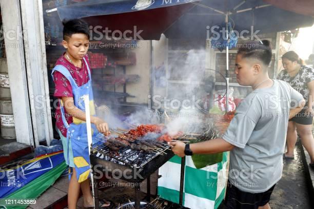 Street food vendor at her food stall sells grilled pork and chicken picture id1211453889?b=1&k=6&m=1211453889&s=612x612&h=lxnkw2qqgufsvropzdnobbexbnqdviolqj8smuutk s=