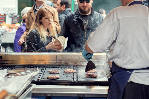 Street Food Vendor Grills Burgers For Customers Stock Photo - Download Image Now