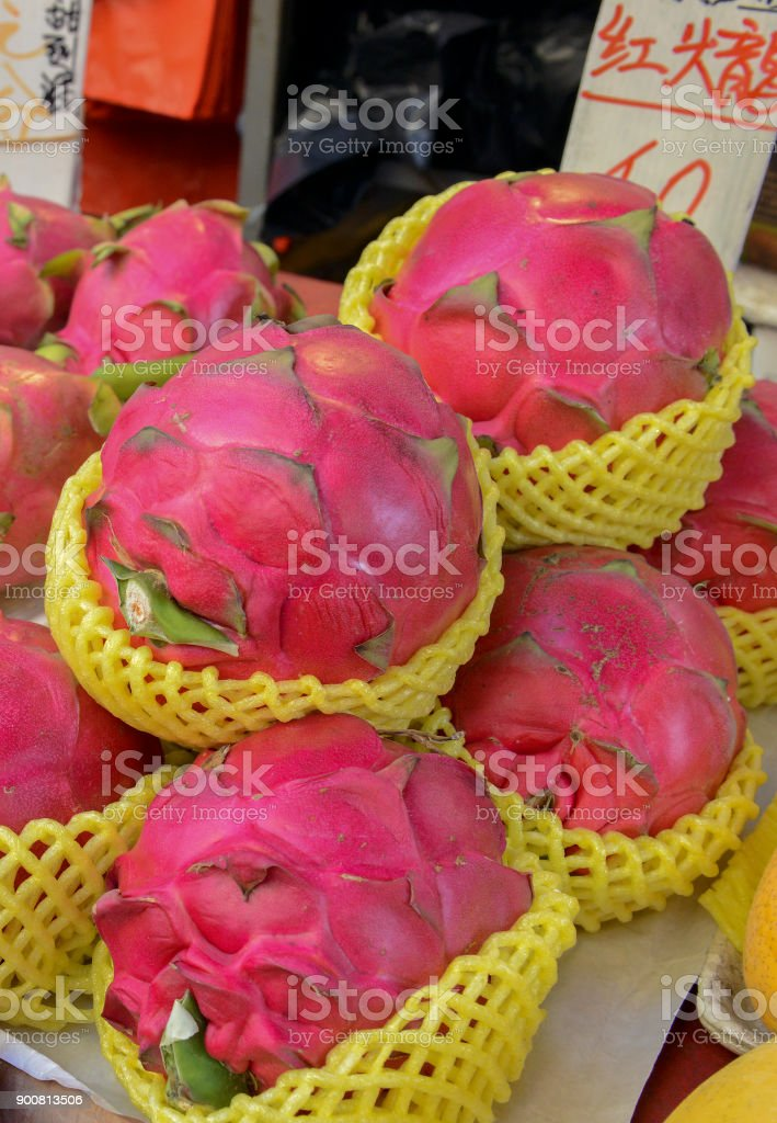 Street food with dragon fruit among various fresh vegetables for sale at Asian market in China stock photo