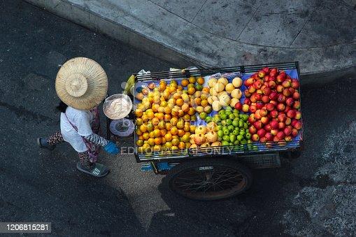 Bangkok, Thailand - December 11, 2019: Street fruit vendor pushes her wheelbarrow in Phaya Thai district of Bangkok.