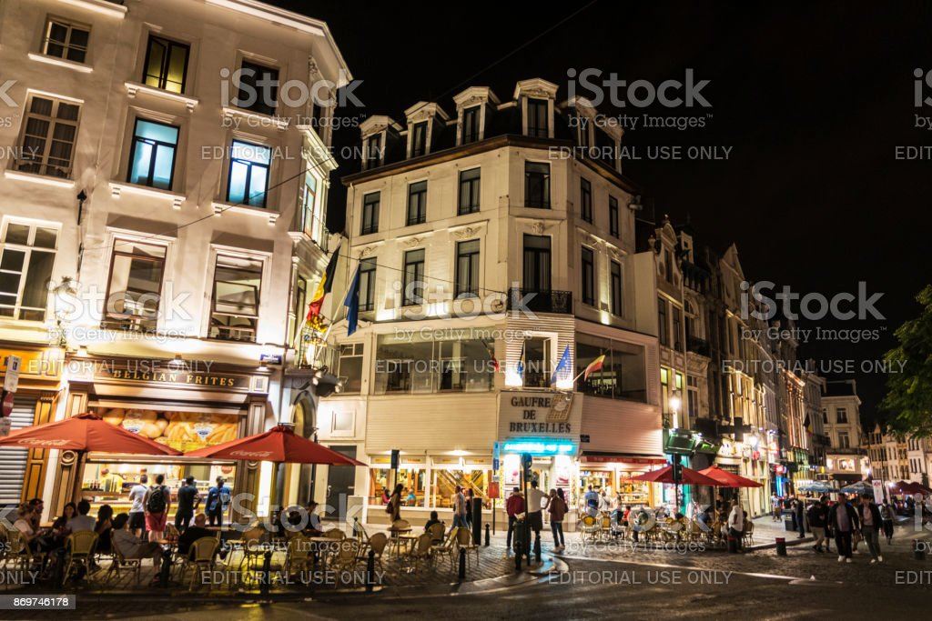 Street full of bars and restaurants with people walking at night...