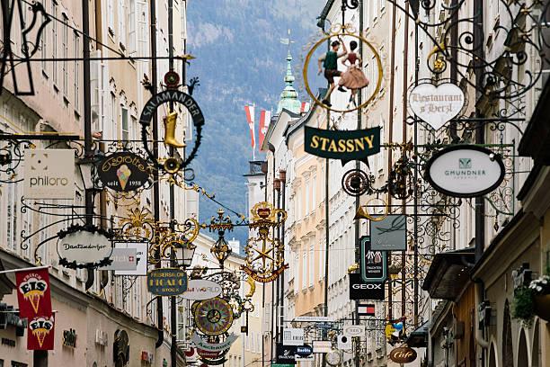 street getreidegasse with multiple advertising signs, salzburg - eisenstadt austria stock-fotos und bilder