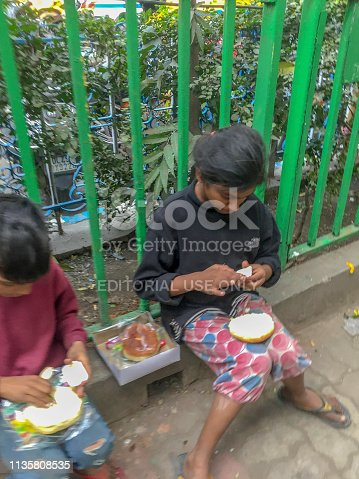 941788480 istock photo Street girl and boy share a meal on the sidewalk 1135808535