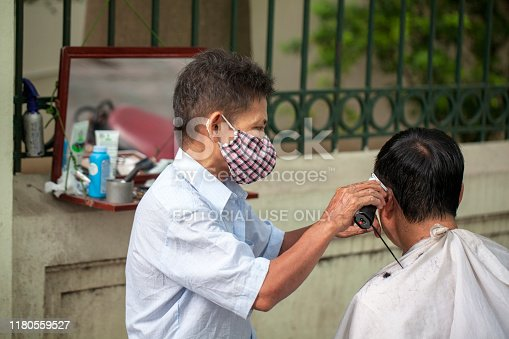 istock Street hairdressers on the streets of Vietnam. Local street barber cutting on the streets of Hanoi. 1180559527