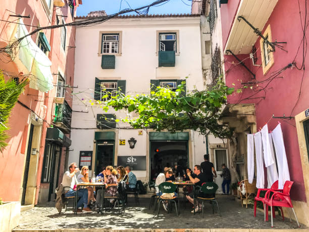 street in alfama district with residential buildings and laundry hanging, lisbon, portugal - people lisbon imagens e fotografias de stock