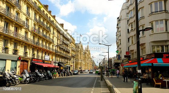 Paris, France - August 14, 2018: A street in central Paris. Apartment buildings, a number of shops and cafes, pedestrian, and vehicular traffic.