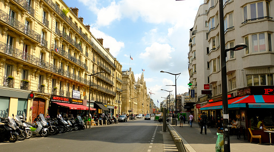 A street in central Paris. Apartment buildings, a number of shops and cafes, pedestrian, and vehicular traffic