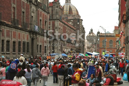 Mexico City, Mexico - February 4, 2007: Street in down town Mexico City. People are walking around in one of the streets in down town Mexico City. It is not a market but several vendors are standing along the street. Historical; facades along the street.