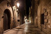Street in old Gothic Quarter (Barri Gotic) of Barcelona city at night, Catalonia, Spain.