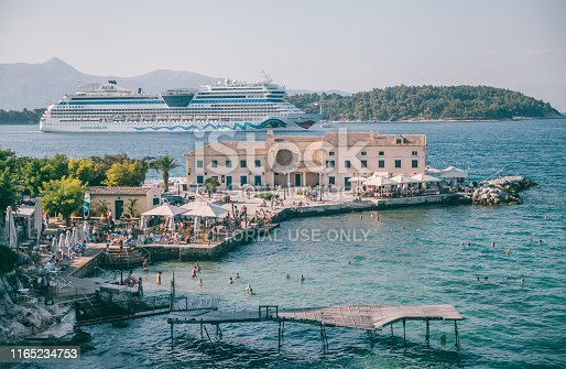 21st July 2019,Corfu,Greece:  Tourists and locals are enjoying swimming in the sea in Corfu. the traditional buildings of Corfu and cafeterias can be seen in the background. Corfu old town is famous for its Venetian colorful buildings and narrow streets.